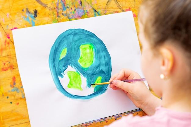 Criança desenha o planeta para o dia da terra. proteção do meio ambiente. celebração do dia da terra. salve o conceito de mundo e unidade.