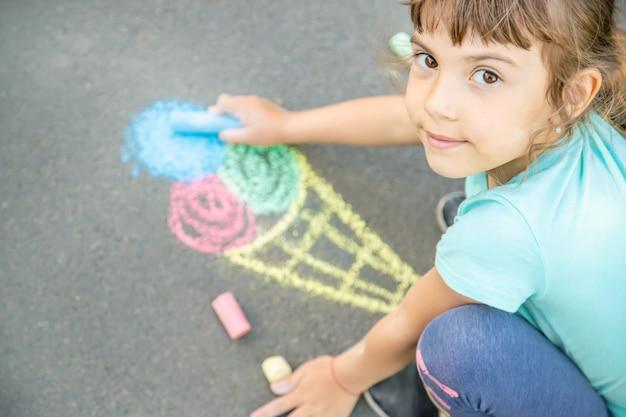 Criança desenha sorvete no asfalto com giz. foco seletivo.