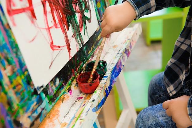 Criança desenha um quadro pinta na aula de arte