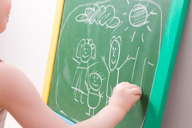 Criança desenhando com giz em uma lousa verde