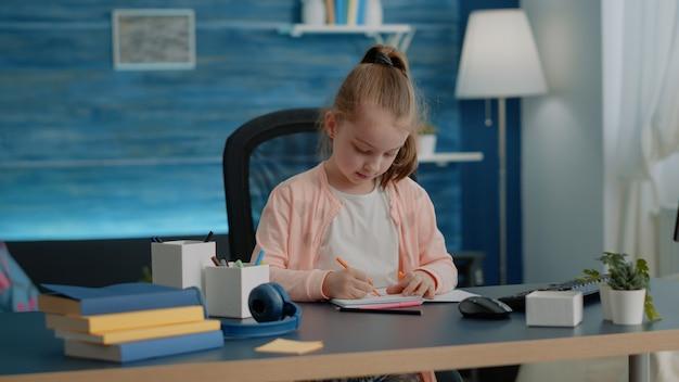 Criança desenhando com lápis coloridos no caderno na mesa