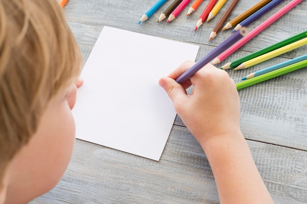 Criança desenhando com lápis coloridos