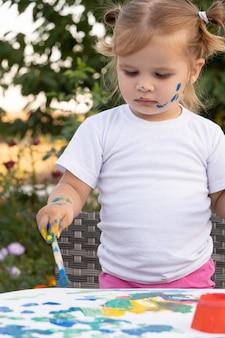 Criança desenhando com tinta e pincel. linda garota pequena pintando foto no jardim, ao ar livre em casa no quintal