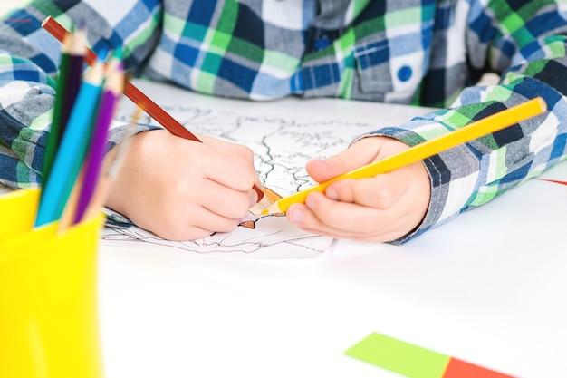 Criança desenho livro de cores com lápis, close-up. criança criando obras de arte coloridas com lápis. de volta à escola. plano de fundo da aula de arte. desenvolvimento infantil e conceito de aprendizagem.
