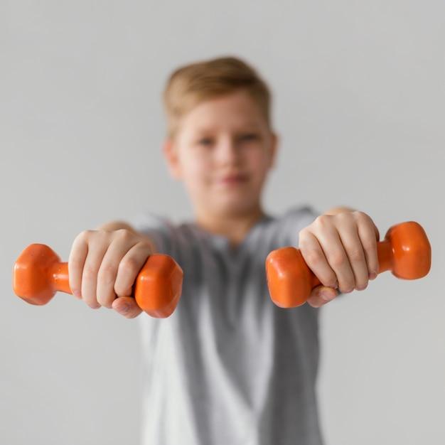 Criança desfocada com tiro médio segurando halteres