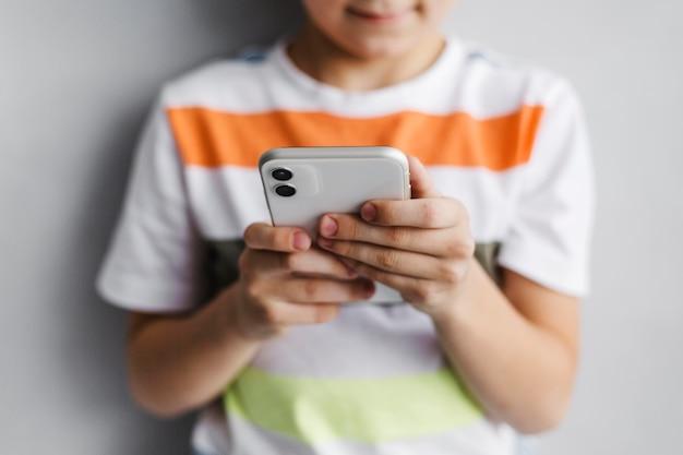 Criança desfocada de frente usando telefone celular
