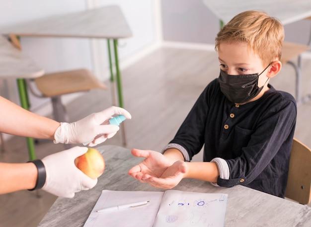 Criança desinfetando as mãos antes de comer uma maçã