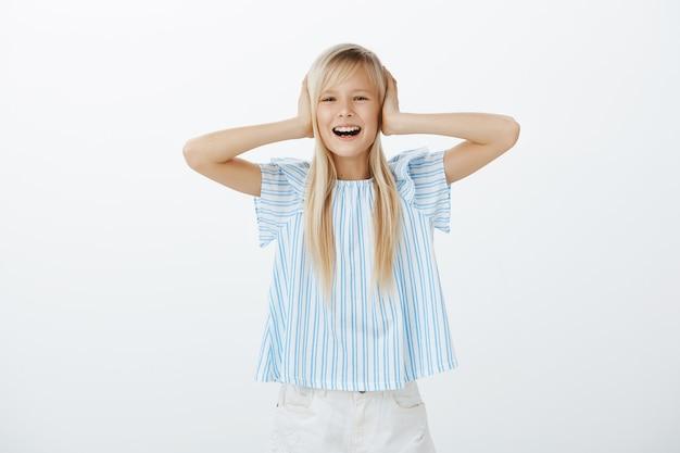 Criança desobediente com mau comportamento em pé sobre uma parede cinza, cobrindo as orelhas com as palmas das mãos e choramingando