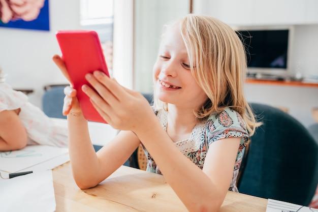 Criança digital nativa do sexo feminino jovem interior em casa usando smartphone