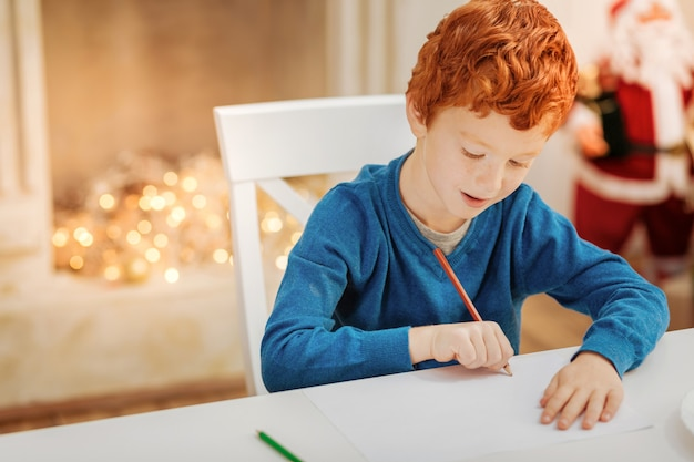 Criança diligente. garoto ruivo encantador sentado em uma mesa e focando sua atenção em um pedaço de papel enquanto escreve sua carta para o papai noel.