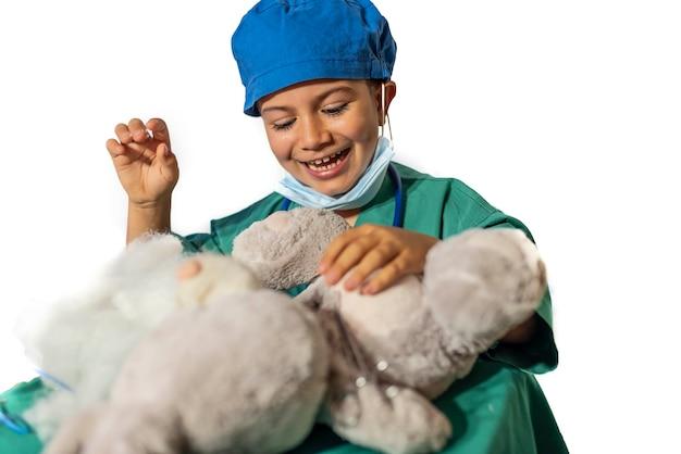 Criança disfarçada de cirurgião opera um ursinho de pelúcia