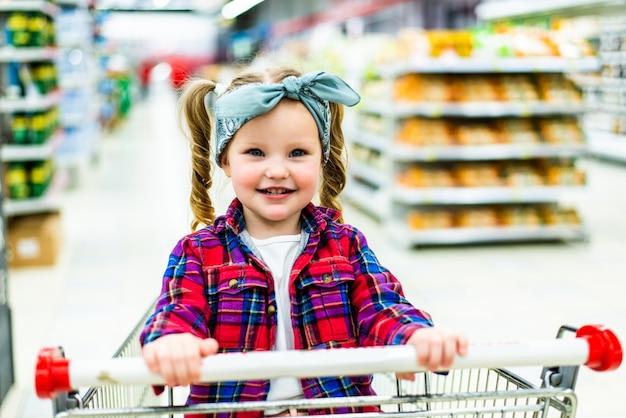 Criança divertida, sentada no carrinho durante as compras da família no hipermercado