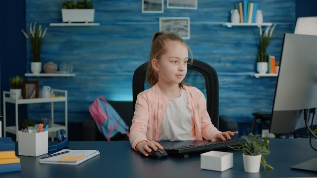 Criança do ensino fundamental usando computador e teclado