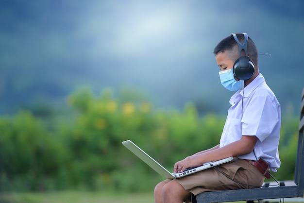 Criança do ensino fundamental usando o laptop