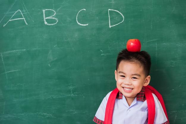 Criança do jardim de infância de uniforme com mochila e maçã vermelha na cabeça