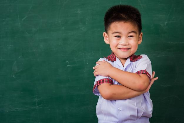 Criança do jardim de infância em uniforme de estudante, sorrindo na lousa verde da escola
