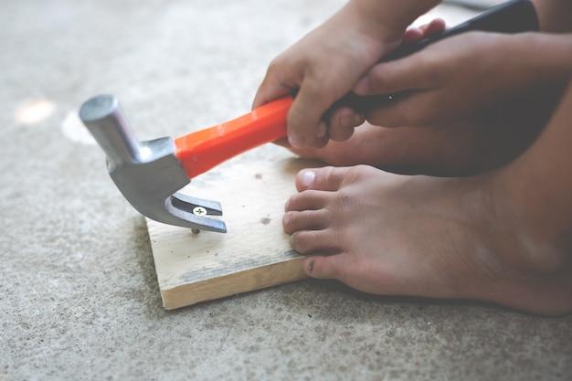 Criança do menino que prende uma ferramenta do martelo.