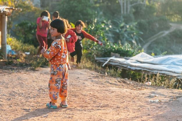 Criança do norte tailandesa vestindo pijamas em pé com a luz do sol e seus amigos