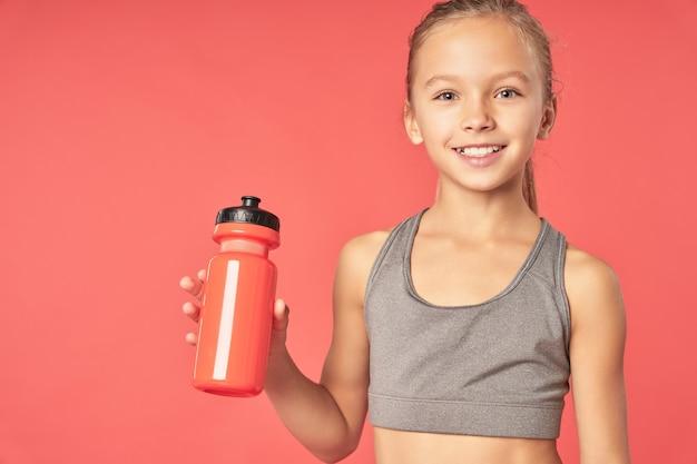 Criança do sexo feminino alegre com uma bebida refrescante, olhando para a câmera e sorrindo em pé contra um fundo vermelho