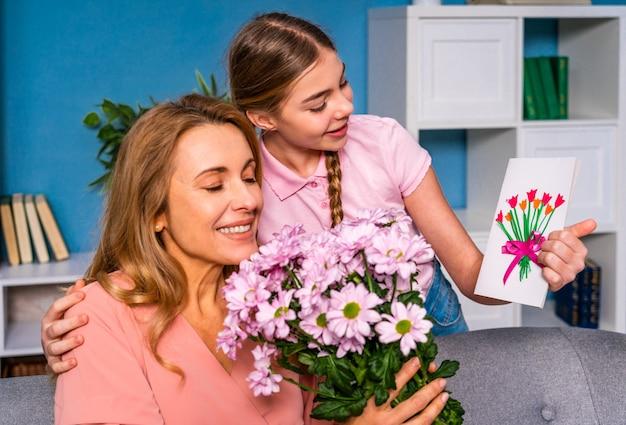 Criança do sexo feminino apresentando flores para a mãe em casa, momentos felizes da vida doméstica