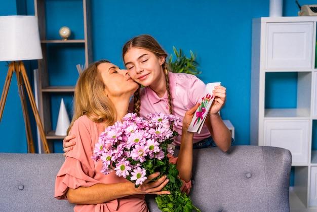 Criança do sexo feminino apresentando flores para a mãe em casa, momentos felizes da vida doméstica Foto Premium