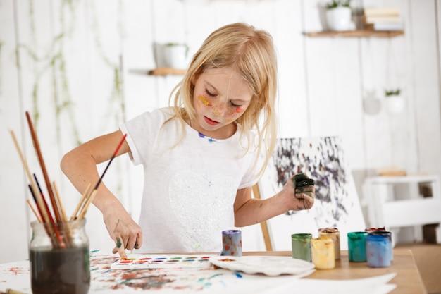 Criança do sexo feminino bonita criativa com cabelo loiro, trabalhando em sua foto na sala de arte