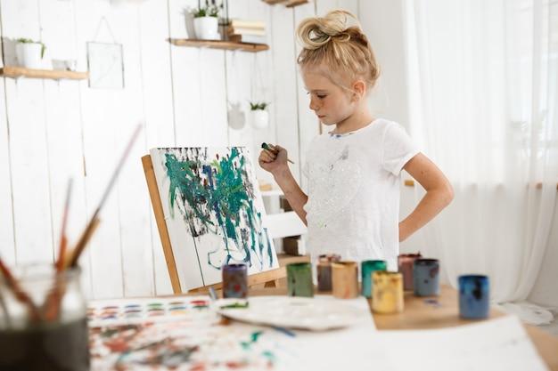 Criança do sexo feminino criativa e ocupada em pé atrás de cavalete, trabalhando em sua nova foto. eu