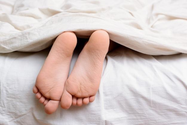 Criança do sexo feminino dorme na cama e seus pés descalços são visíveis debaixo do cobertor