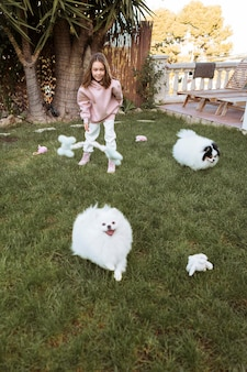 Criança do sexo feminino e cachorro fofinho brincando