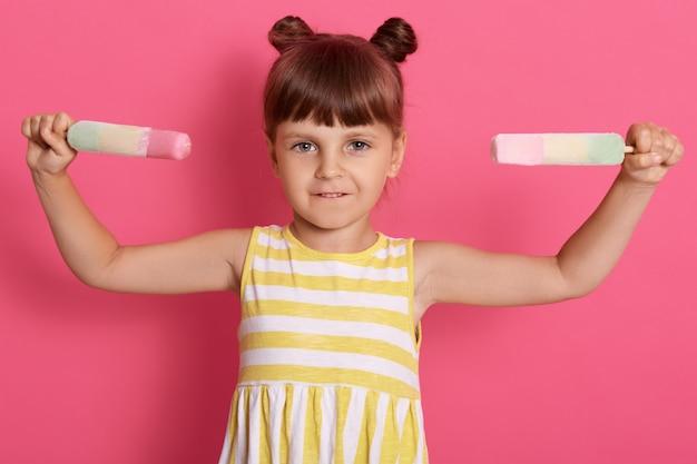 Criança do sexo feminino encantadora segurando dois sorvete nas mãos, se divertindo, quer comer sorvete saboroso, posando isolado sobre parede rosada.