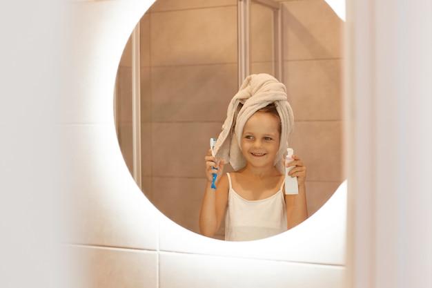 Criança do sexo feminino escovando os dentes no banheiro, olhando seu reflexo no espelho com expressão facial positiva e sorriso, vestindo camiseta branca e enrolou o cabelo na toalha.