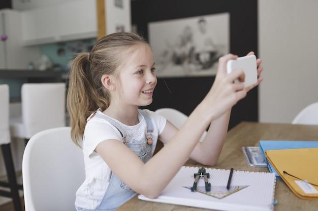 Criança do sexo feminino fazendo videochamadas com um amigo sorrindo de casa
