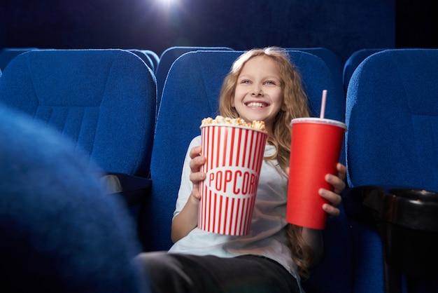 Criança do sexo feminino feliz desfrutando filme engraçado no cinema