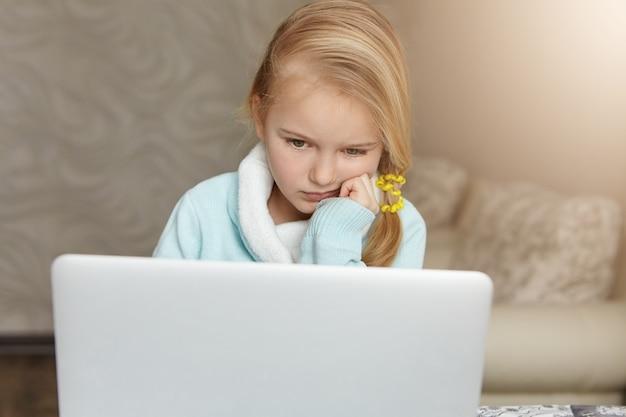 Criança do sexo feminino fofa e infeliz com cabelo bagunçado segurando a mão no queixo enquanto faz a lição de casa