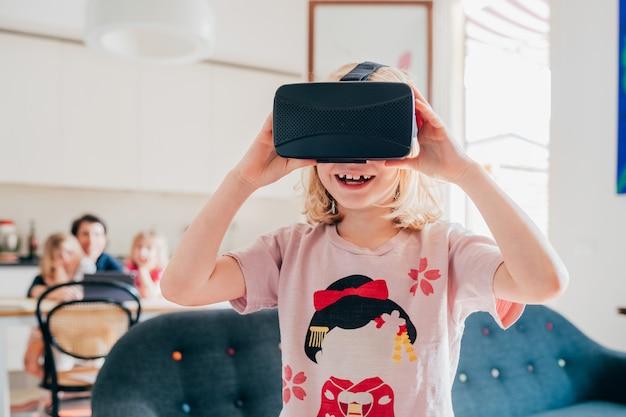 Criança do sexo feminino interior usando o visualizador em 3d