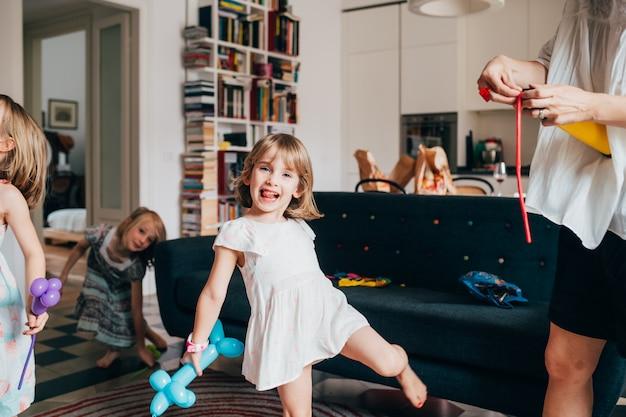 Criança do sexo feminino linda jovem interior em casa brincando com balão sorrindo
