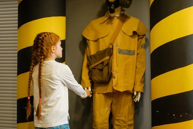 Criança do sexo feminino olhando para manequim de bombeiro
