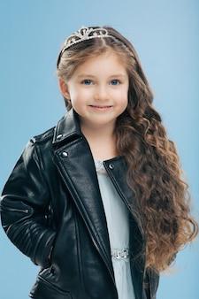 Criança do sexo feminino pequena atraente tem longos cabelos cacheados, usa sorrisos de coroa e jaqueta de couro isolados positivamente sobre parede azul