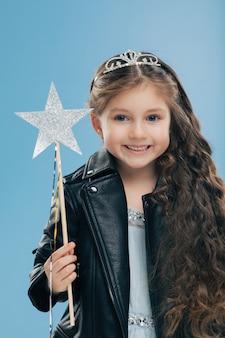 Criança do sexo feminino pequena satisfeita tem longos cabelos cacheados, vestidos com jaqueta de couro preta