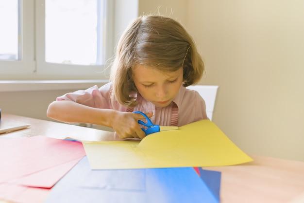 Criança do sexo feminino senta-se em casa à mesa, papel colorido de tesoura