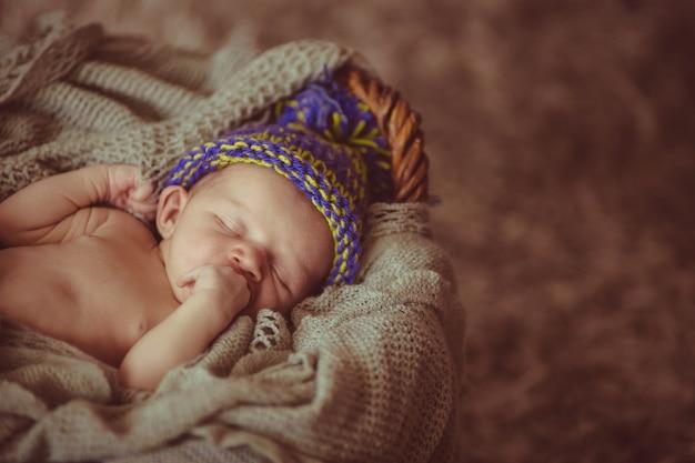 Criança doce em chapéu de lã dorme na cesta
