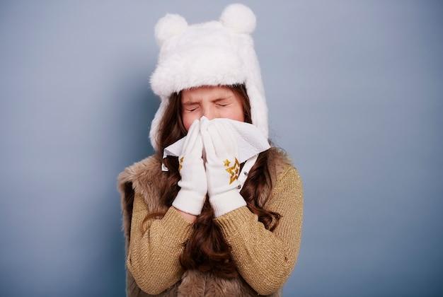 Criança doente assoando o nariz