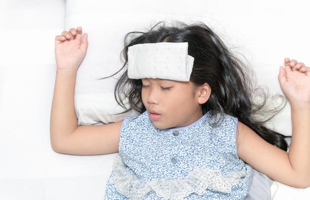 Criança doente com febre alta, deitado na cama.