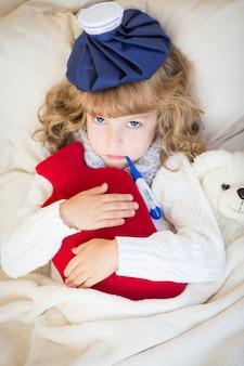 Criança doente com febre e bolsa de água quente em casa