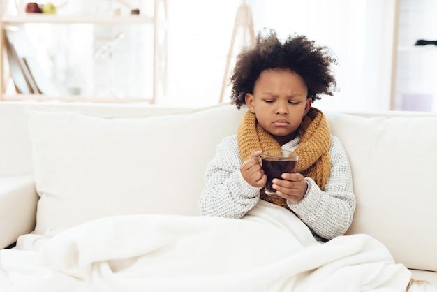Criança doente com gripe no lenço que senta-se no sofá em casa.