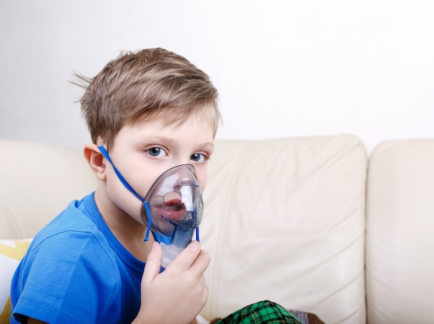 Criança doente com nebulizador pediátrico, olhando para a câmera