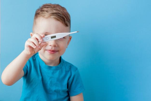 Criança doente com um termômetro, medindo a altura de sua febre e olhando para a câmera.