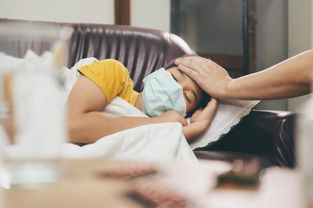 Criança doente, deitado no sofá-cama com máscara de proteção no rosto contra infecção