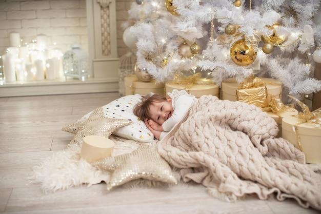 Criança dorme debaixo de uma árvore de natal