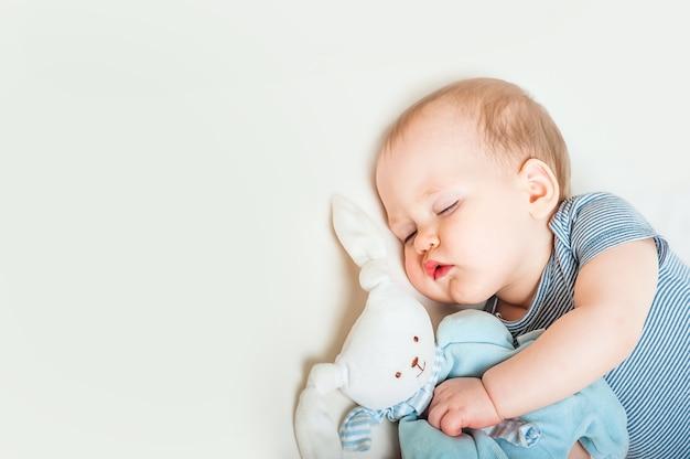 Criança dormindo com lebre de brinquedo na cama closeup conceito de sono de bebê saudável e espaço de cópia